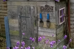 A rustic shed made completely from reclaimed pallet wood