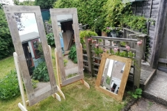 a pair of stund up mirrors plus a large wall mirror all framed in pallet wood